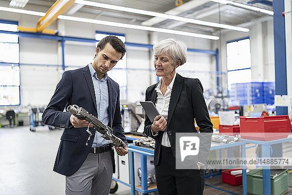 Geschäftsmann und leitende Geschäftsfrau bei der Untersuchung von Werkstücken in einer Fabrik