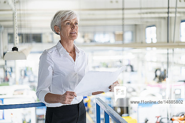 Senior woman holding plan in a factory