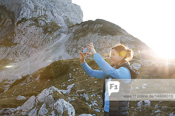 Austria  Tyrol  woman taking cell phone picture in mountainscape at sunset