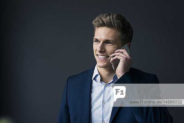 Portrait of smiling young businessman on cell phone