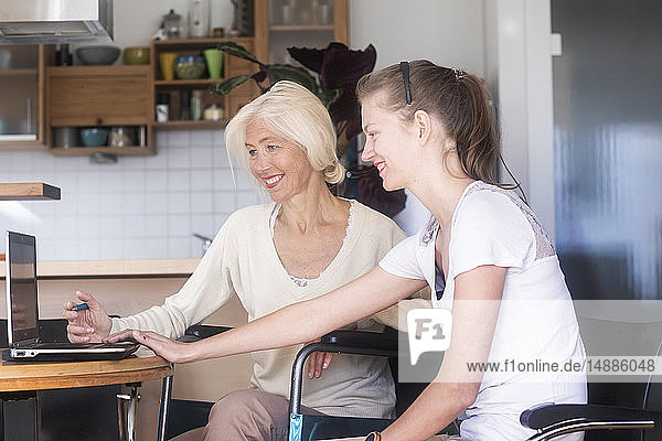 Daughter and mother in a wheelchair using a laptop