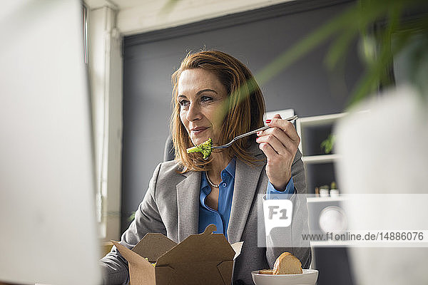 Businesswoman sitting in office  working on PC  eating lunch
