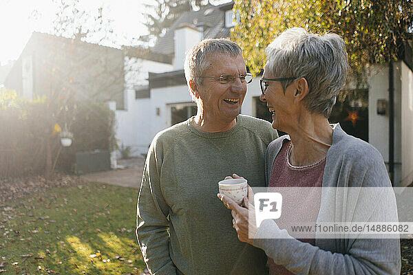 Glückliches älteres Ehepaar mit einer Tasse Kaffee im Garten