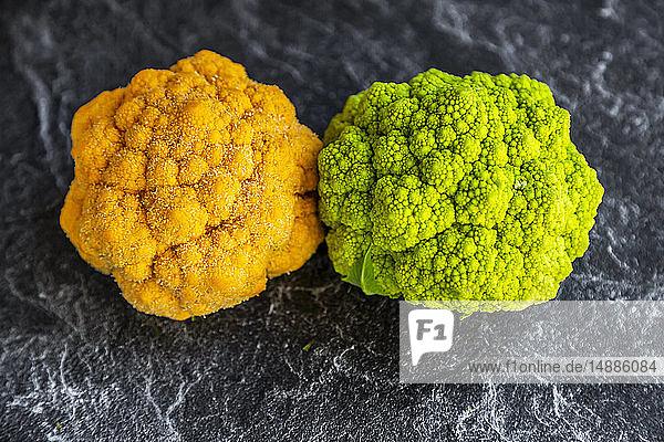 Yellow and bright green cauliflower on slate