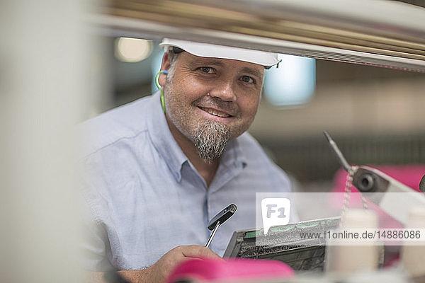 Porträt eines lächelnden Mannes mit Schutzhelm in einer Fabrik