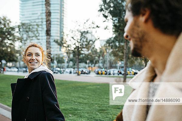 Lächelnde junge Frau dreht sich um und sieht ihren Freund an