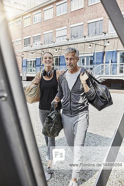 Porträt eines reifen Mannes und einer jungen Frau mit Sporttasche auf dem Weg zum Fitnessstudio