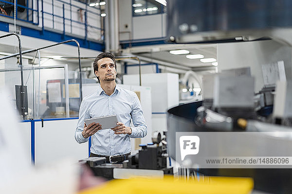 Businessman holding tablet and looking at a machine in a factory