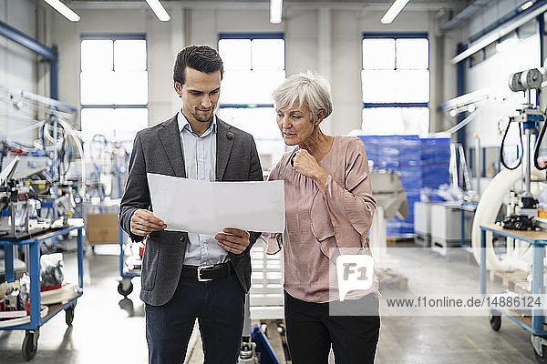 Businessman and senior woman looking at plan in a factory
