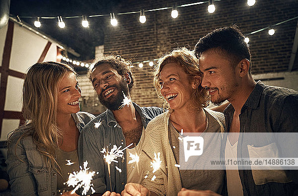 Freinds having a backyard party  burning sparklers