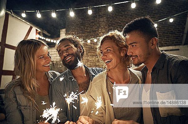 Freunde feiern eine Gartenparty  brennen Wunderkerzen