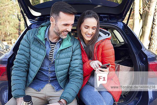 Ehepaar benutzt Smartphone  während es während einer Autofahrt im Kofferraum sitzt