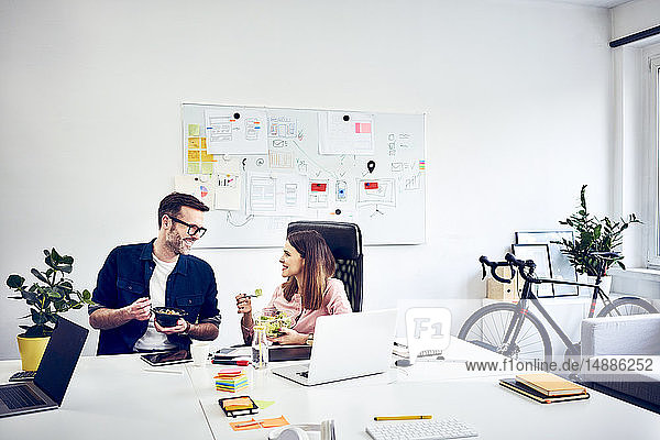 Zwei Kollegen unterhalten sich in der Mittagspause im Büro