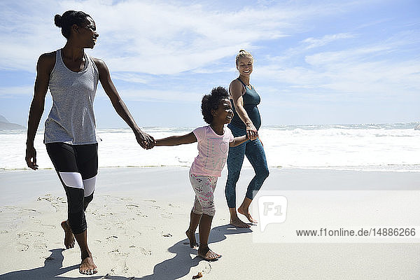 Happy mother with daughter and friend walking on the beach