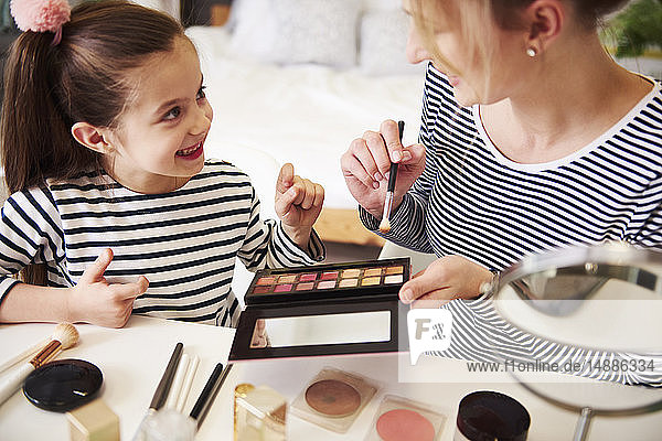 Mother and daughter applying make up together  using blusher