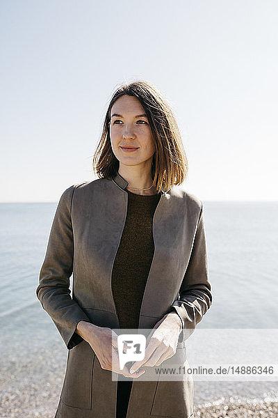 Zuversichtliche Frau steht am Meer