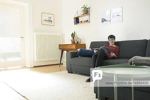 Lässige kurzhaarige Frau entspannt sich auf einer Couch im Wohnzimmer und liest eine Zeitschrift