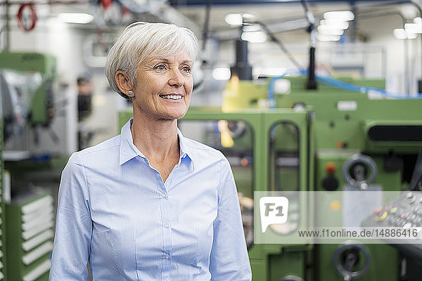 Portrait of smiling senior businesswoman in a factory looking around
