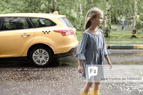 Mädchen in blauem Kleid  überquert die Straße  gelbes Auto im Hintergrund