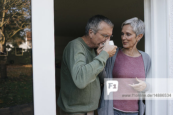 Älteres Ehepaar trinkt Kaffee an der Terrassentür
