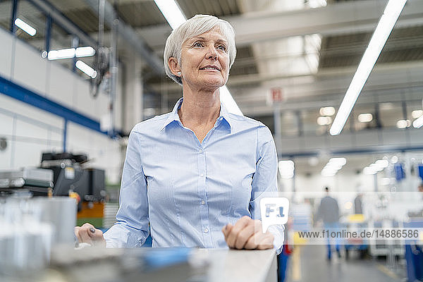 Senior businesswoman in a factory looking around