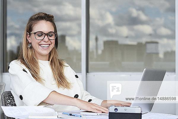 Porträt einer lachenden jungen Geschäftsfrau  die im Büro am Laptop arbeitet