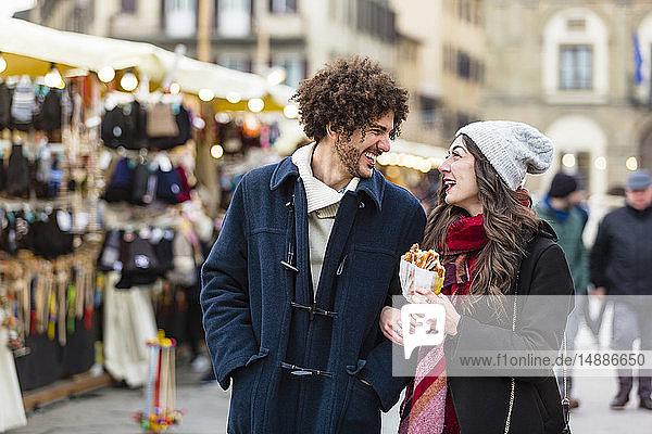 Glückliches junges Paar schlendert auf dem Weihnachtsmarkt
