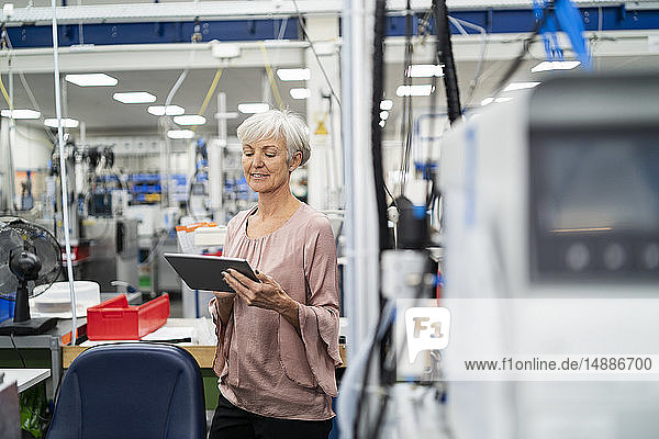 Smiling senior woman using tablet in a factory