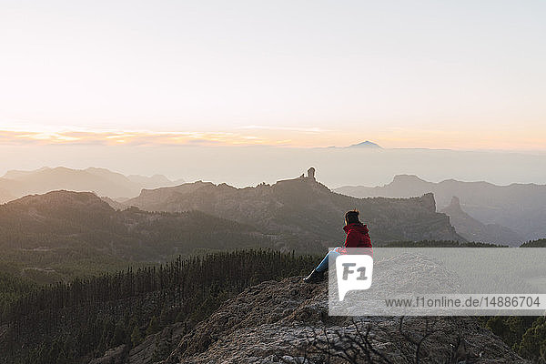 Spain  Gran Canaria  Pico de las Nieves  woman sitting on rock looking at view
