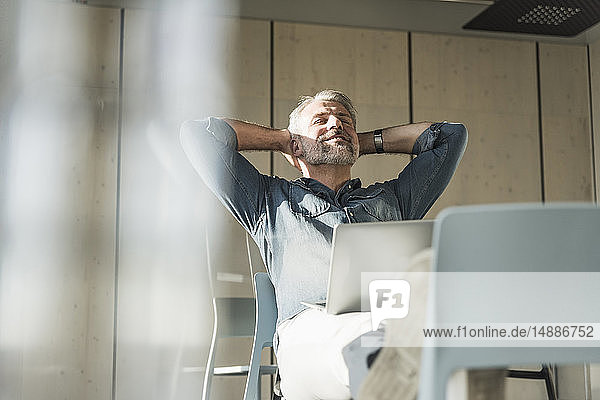 Casual mature businessman with laptop leaning back