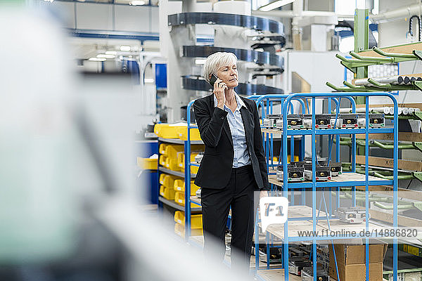 Senior businesswoman on cell phone in a factory