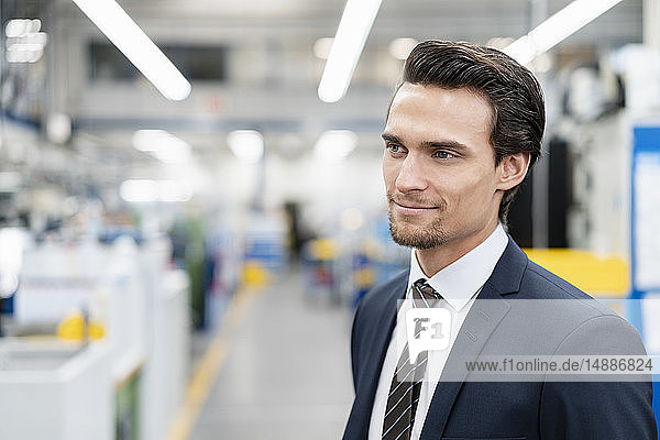 Portrait of confident businessman in a factory looking around