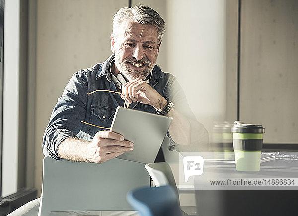 Lächelnder  lässiger  reifer Geschäftsmann am Schreibtisch sitzend mit Tablett