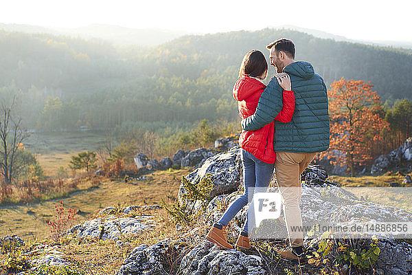 Rückansicht eines auf Fels stehenden Paares auf einer Wanderung in den Bergen