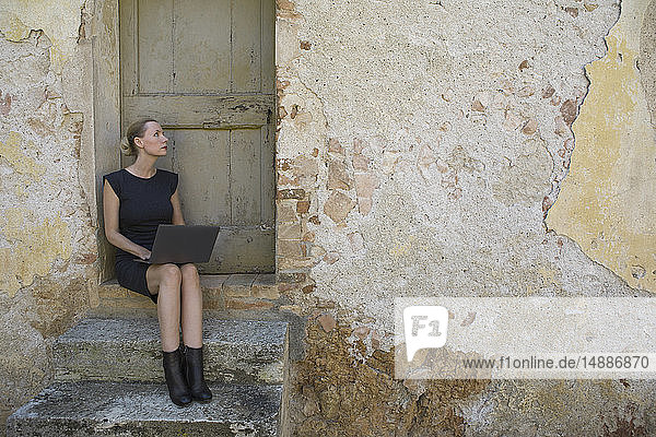 Italy  Tuscany  Monteriggioni  woman sitting at house entrance using laptop