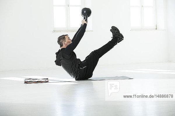 Mann macht sein Fitness-Regime  macht Kesselglocken-Sit-ups