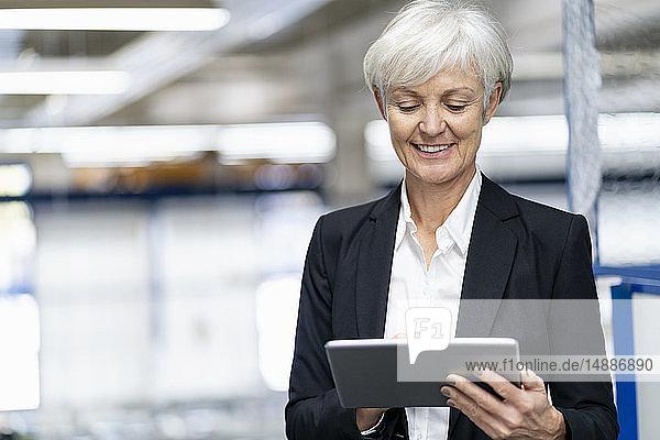 Lächelnde ältere Geschäftsfrau mit Tablette in einer Fabrik