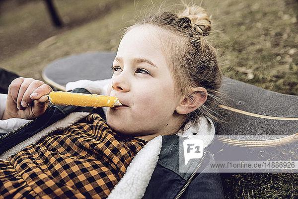 Kleines Mädchen isst Eiscreme  ruht Kopf auf Skateboard