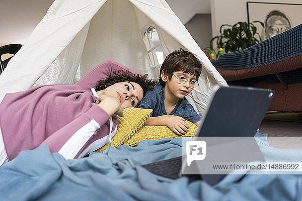 Mutter und Sohn liegen im Spielzelt und schauen einen Film auf einem Tablett