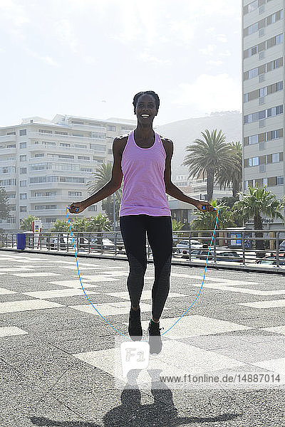 Sportliche Frau beim Seilspringen im Freien