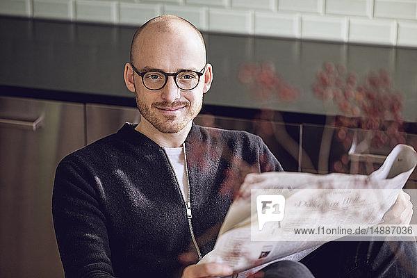 Mann sitzt in der Küche und liest Zeitung