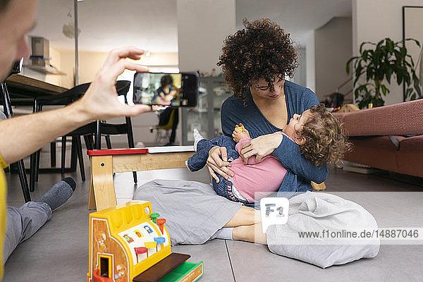 Mutter und Tochter spielen im Wohnzimmer  bevor sie Smartphone-Fotos machen