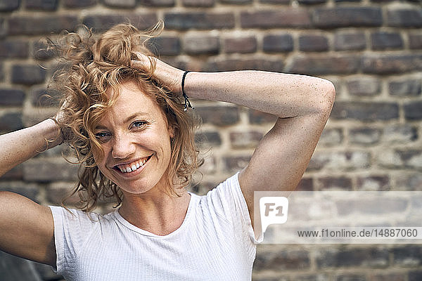 Portrait of a young woman in front of a brick wall  with hands in hair