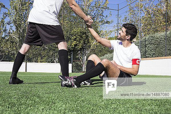 Football player helping an injured player during a match