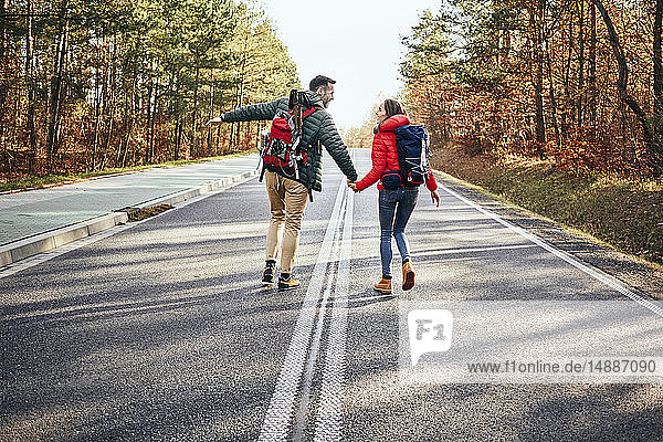 Happy couple walking in middle of an empty road in the woods