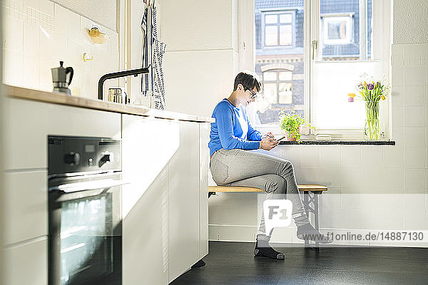 Short-haired woman sitting on bench in kitchen at the window using smartphone