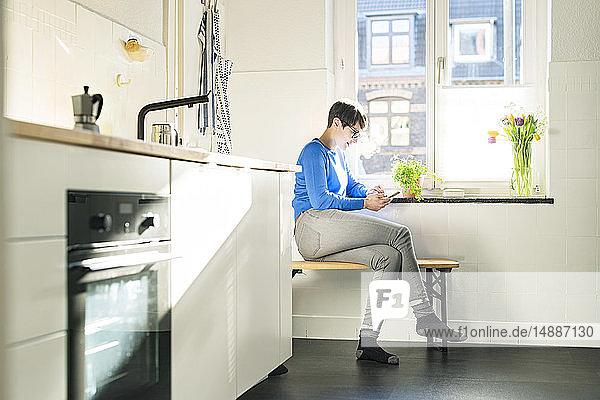 Kurzhaarige Frau sitzt auf einer Bank in der Küche am Fenster und benutzt ein Smartphone