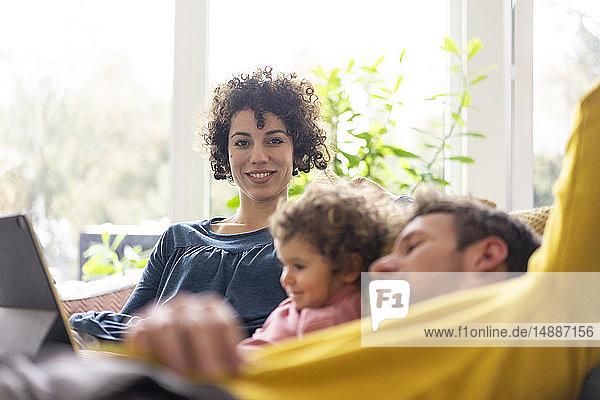 Familie liegt auf der Couch und schaut einen Film auf dem Tablett