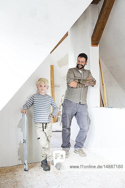 Porträt eines lächelnden Vaters und eines lächelnden Sohnes bei der Dachbodenumrüstung