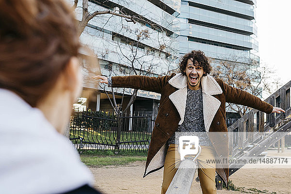 Überschwängliches Paar auf einer Wippe auf einem Spielplatz